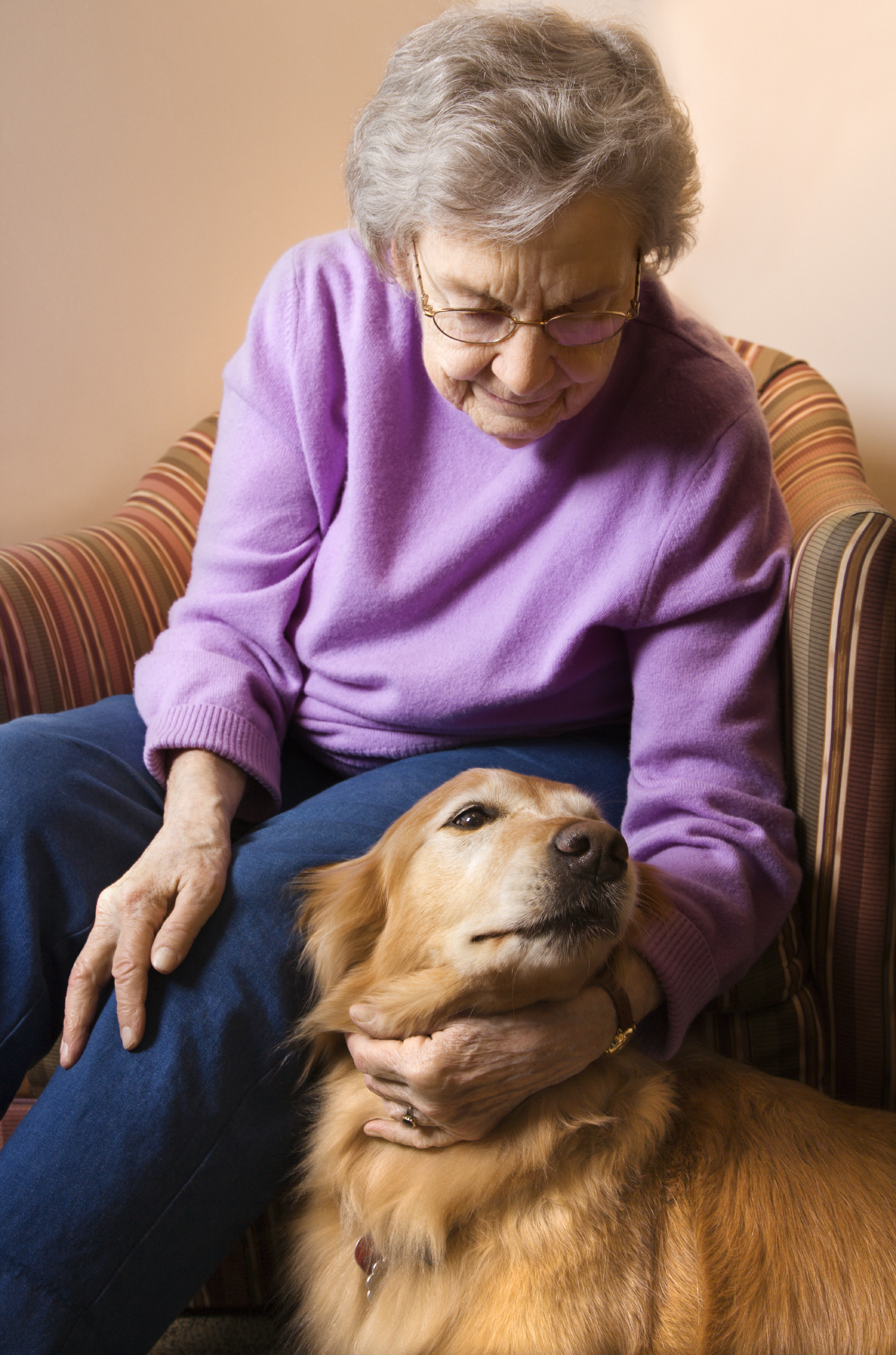 An Older Woman Sitting in a Chair Petting Her Dog